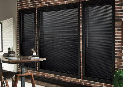 black aluminum blinds against brick wall