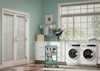 aluminum blinds against teal wall in laundry room