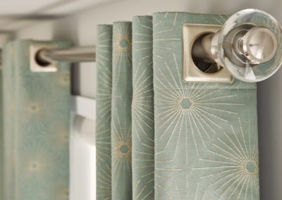 close up of curtain rod and green geometric curtains