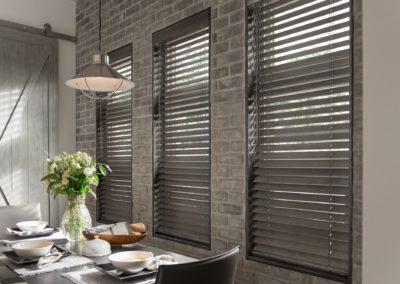 gray blinds on gray brick wall