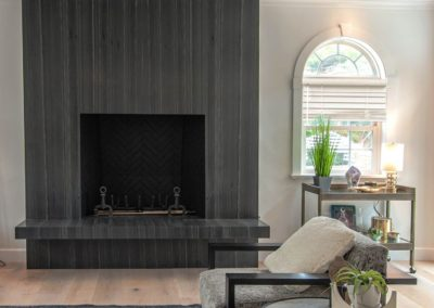 vertical blinds along wall in living room with black fire place