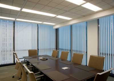 vertical blinds in conference room with long table and chairs
